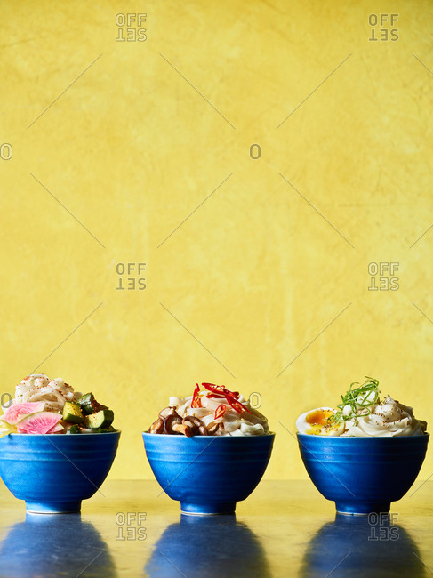 Three Asian noodle pasta in blue bowls on yellow background