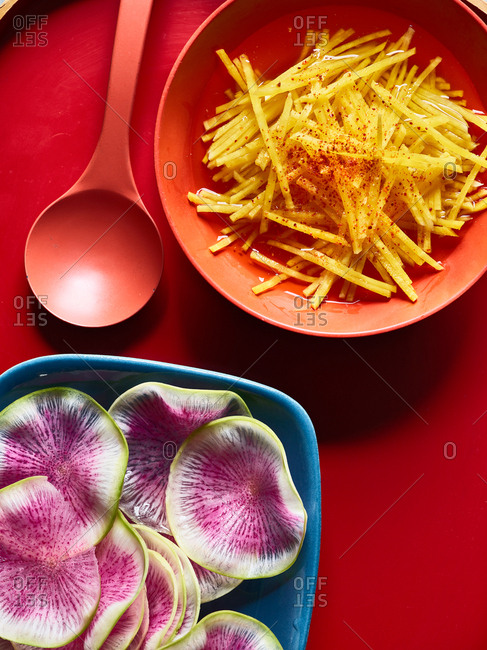 Overhead view of Asian pickled vegetables on red surface