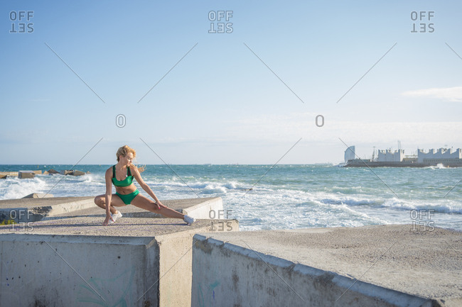 Russian blonde woman in bikini doing stretches on the coast of Barcelona, Spain