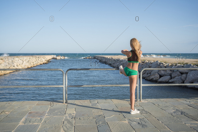 Beautiful Russian woman in bikini doing stretches on the coast of Barcelona, Spain