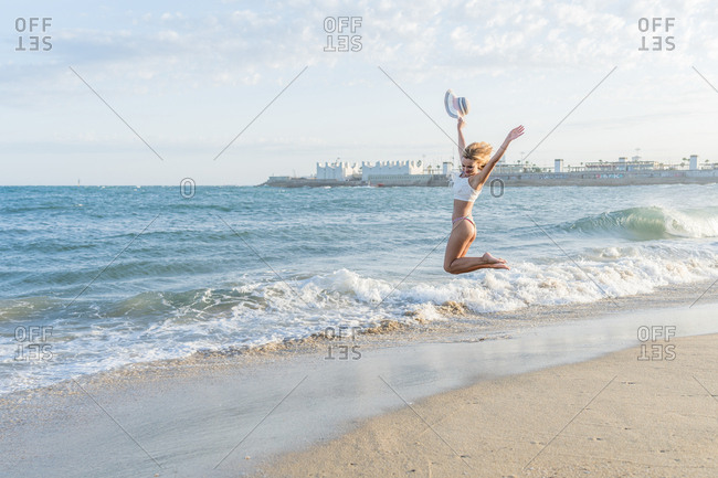Happy smiling blonde woman jumps up and down while waving her hat on the shore of the beach.