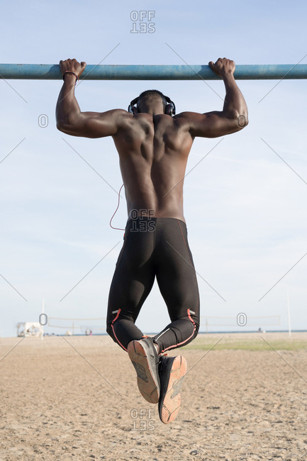 Muscular and attractive black man does sport on the beach. Rear view