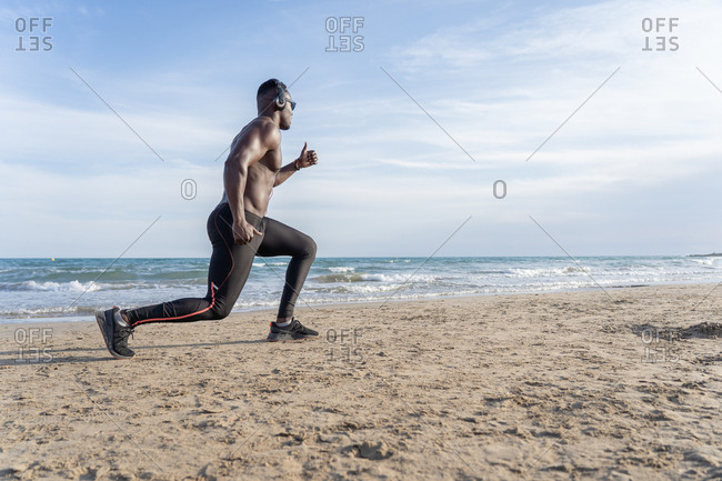 Muscular and attractive black man does sport on the beach