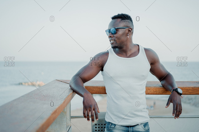 Young black man leaning on a railing looking at the sea dressed in jeans and sunglasses