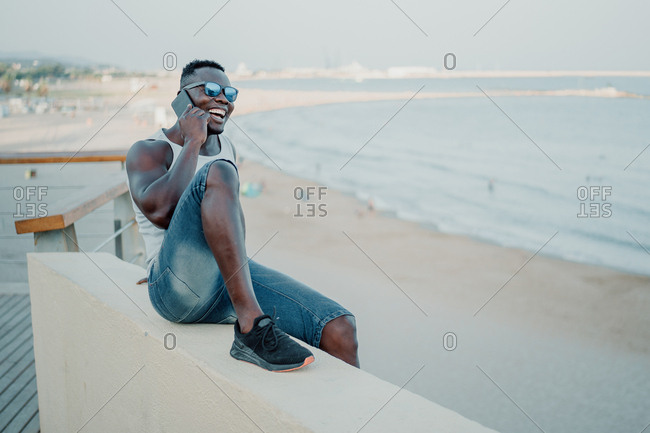 A young black man on the beach talking on his cell phone. While he is looking at the sea. Copy space big