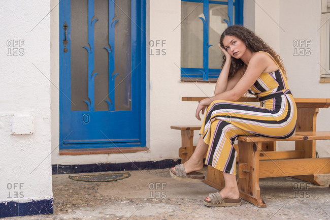Beautiful woman with curly hair and green eyes, dressed in yellow, looks at the camera with a lost look as she sits in front of her house.