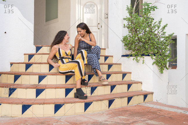 wo beautiful women tell each other their gossip sitting on the stairs of a building