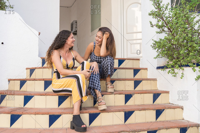 two beautiful women tell each other their gossip sitting on the stairs of a building
