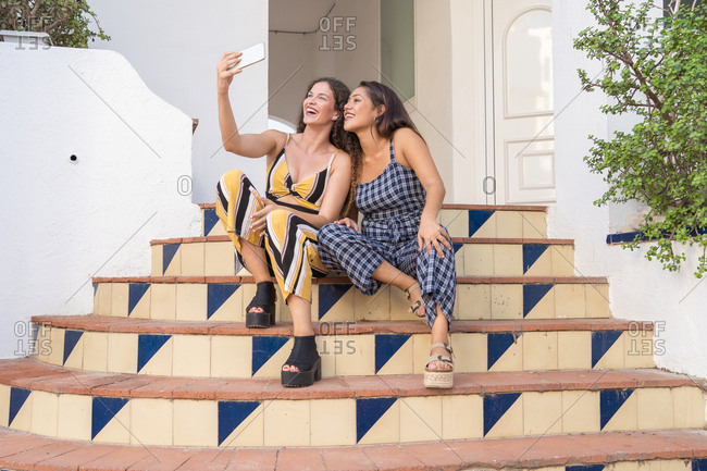 two beautiful women happily make a selfie sitting on the stairs of a building