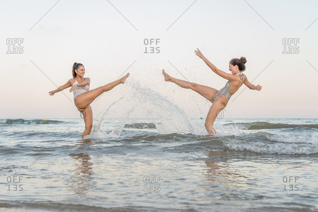 two beautiful young women play with water in the sea