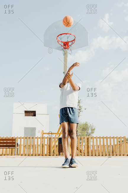 Black boy dressed with white t-shirt strip to basket with backs to the hoop