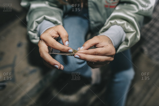 Close up of young hands rolling a weed cigarette in urban location