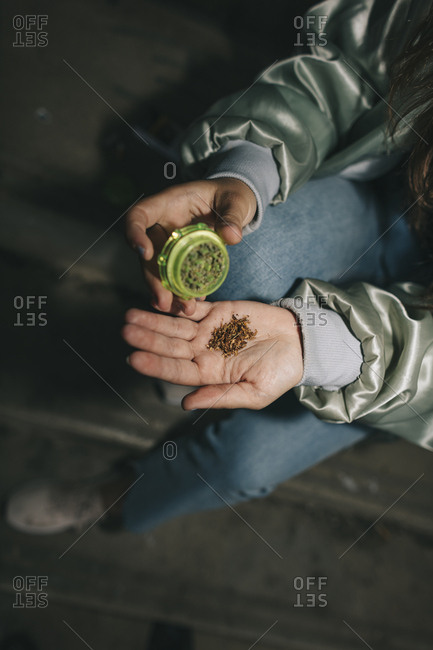 Close up of the hands of a female with a grinder, tobacco and marijuana