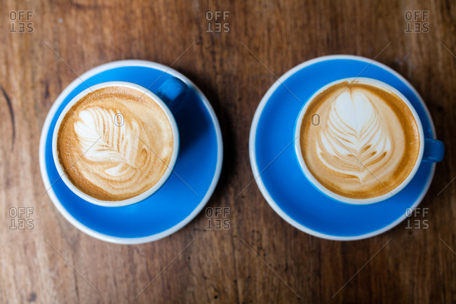 Overhead view of two freshly made cappuccinos