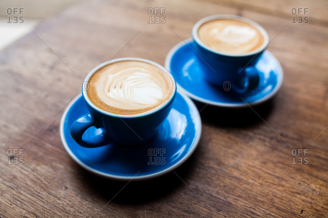 Two freshly made cappuccinos in blue mugs