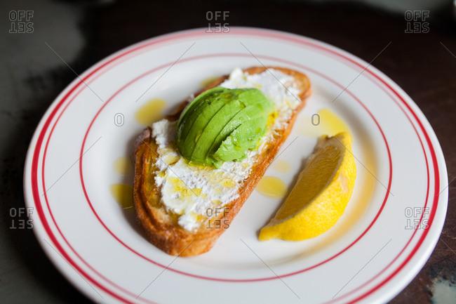 Avocado toast on a plate with lemon
