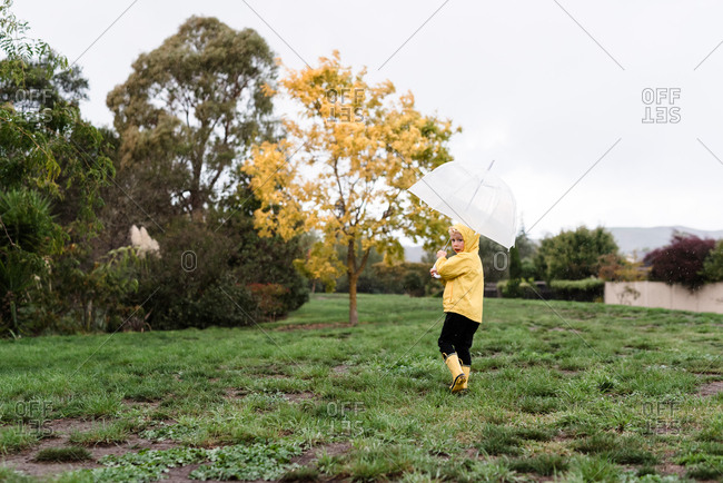Adorable blonde boy running with umbrella in the rain