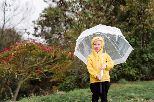 Cute kid posing in backyard with umbrella on a rainy day