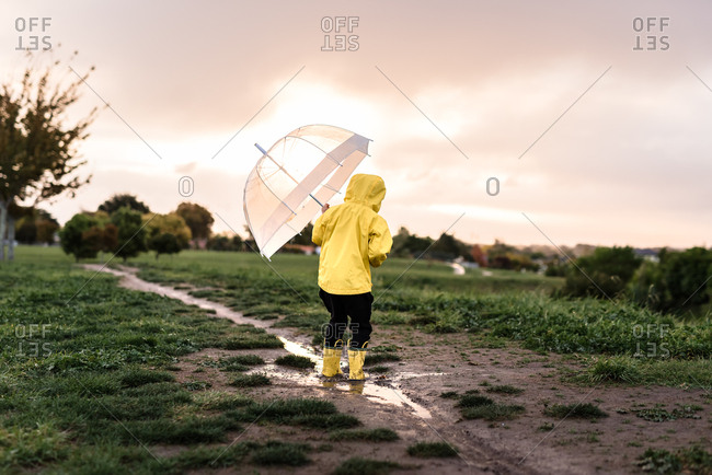 Child jumping in mud with an umbrella