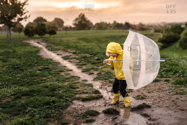 Young boy playing in a mud puddle in the rain