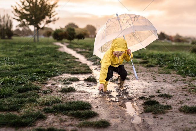 Young child playing in a mud puddle