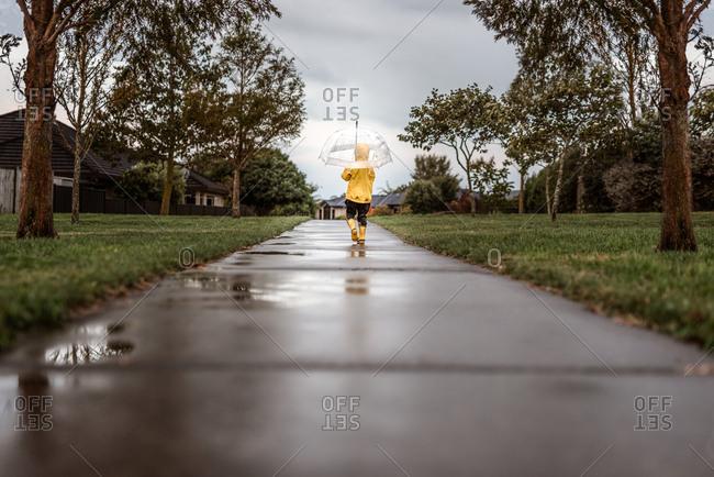 Child walking on sidewalk in the rain