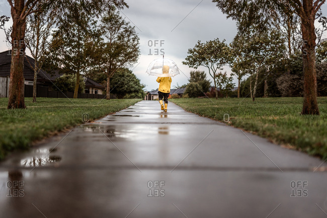 Child walking on sidewalk in the rain