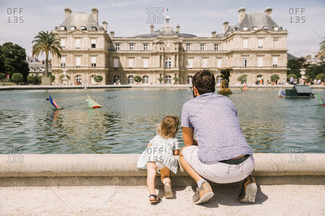 A father and his toddler daughter watch the boats in the Jardin de Luxembourg in Paris