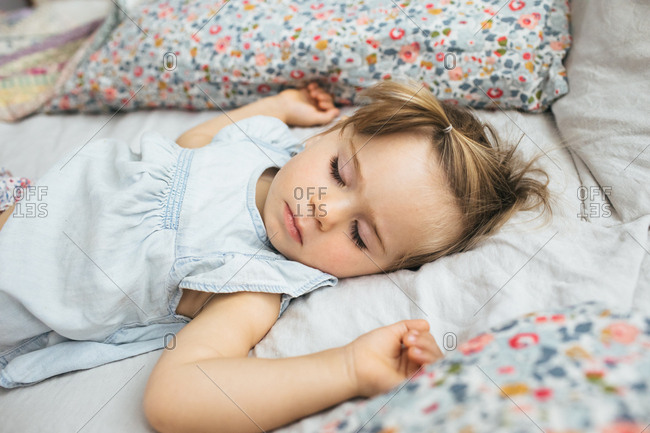 A toddler girl naps on a bed in a bright room surrounded by pillows
