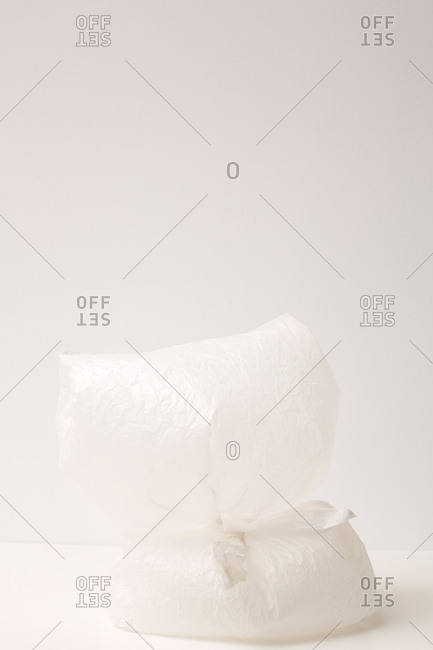Two inflated white plastic bags against white wall background installation
