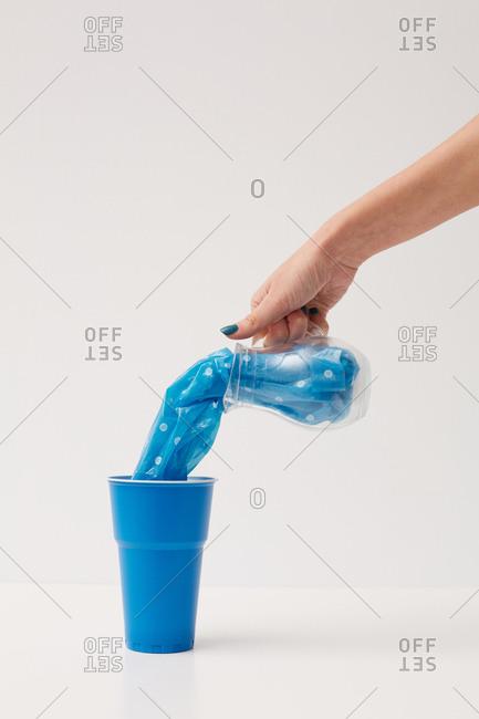 Unrecognizable woman pouring blue plastic bag into blue plastic cup conceptual shot