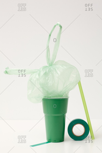 Emerald-green cup, tape, light green straw and plastic bag installation