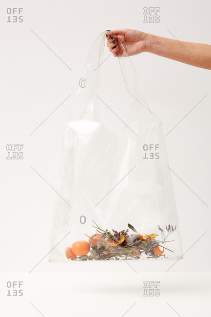 Hand of unrecognizable woman holding transparent plastic bag with herbs, tangerine skin and tangerines in it
