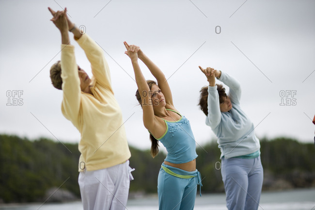 Young adult girl doing yoga with her mid-adult mother and mature grandmother on a beach.