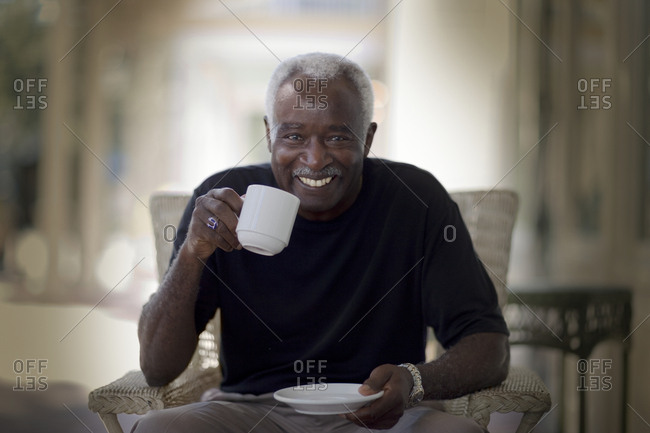 Portrait of a smiling mature adult man drinking tea.
