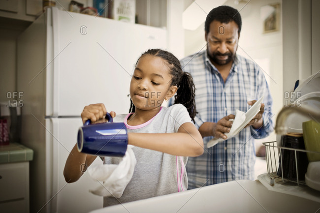 Girl drying dishes with her mid-adult father in a kitchen.