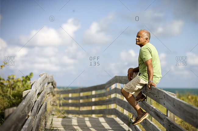 Mature adult man sitting on a wooden fence.