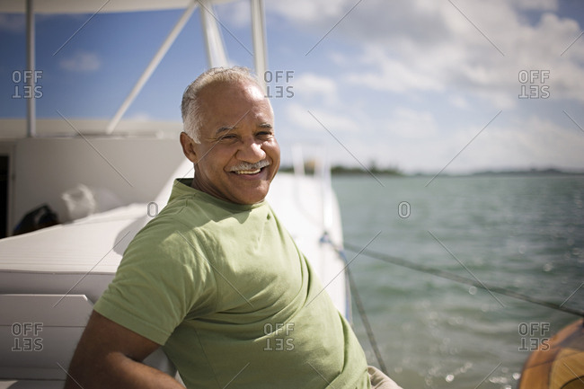 Portrait of a mature adult man sitting on a boat.