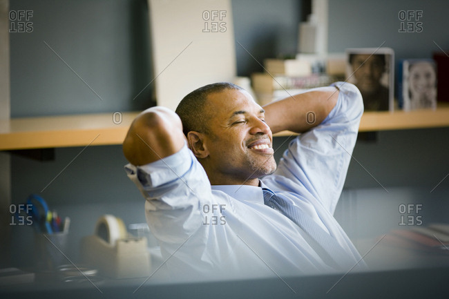 Smiling mid-adult businessman leaning back with his hands behind his head in his office.