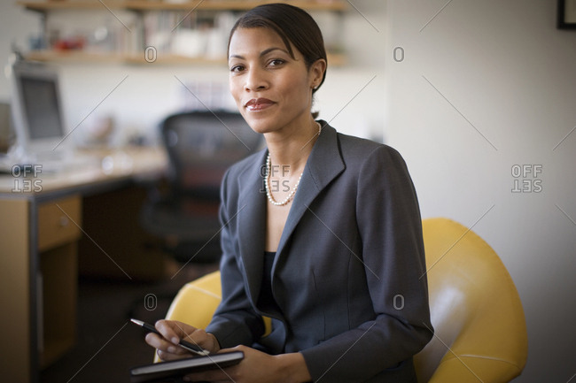 Portrait of a confident mid-adult businesswoman holding a notebook and pen while sitting inside her office.