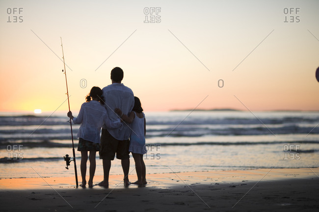 Man and his two daughters standing on the beach holding fishing rods and watching the sun set