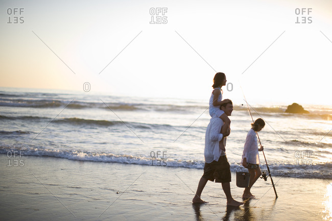 Father and two daughters walking on the beach with fishing rod