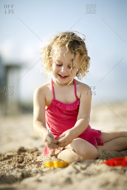Young girl sitting on the beach in a bathing suit.
