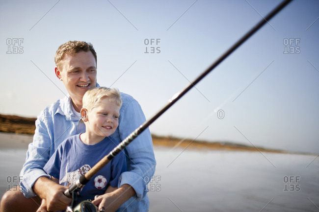 Smiling father and son fishing at a beach.