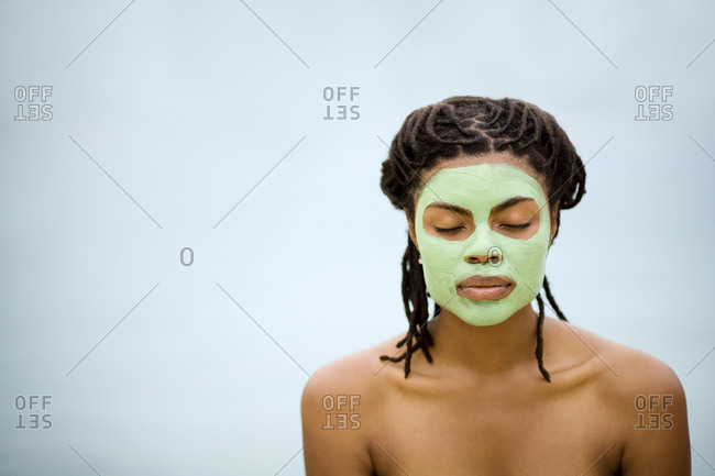 Young woman with a green face mask.