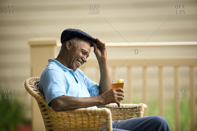 Senior man laughing while sitting in a wicker chair with a cold drink.