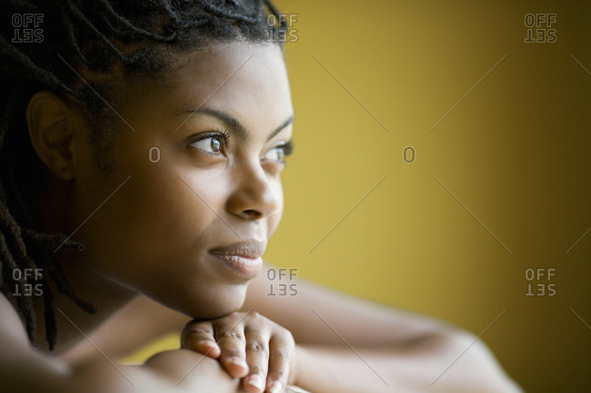 Contemplative young woman resting her chin on her hand.