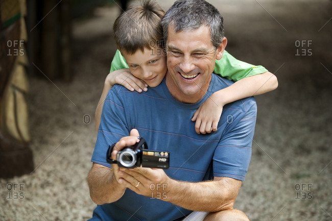 Laughing mid adult man holding a video camera while crouching with his young son inside a nature reserve.