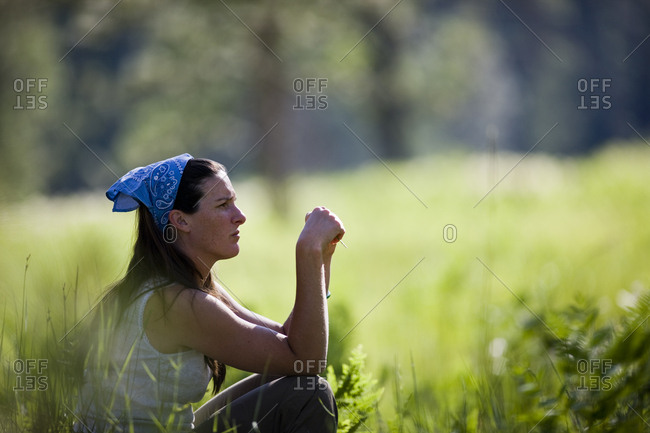 Mid-adult woman sitting in long grass.