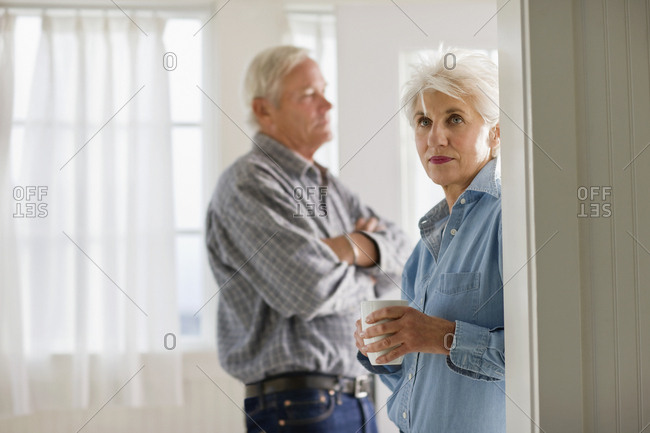 Mature adult couple standing having a drink in a room.